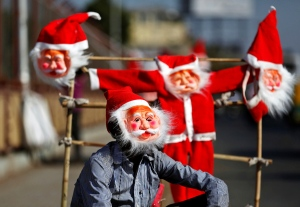 A vendor wears a Santa Claus mask to attract customers on a roadside in Ahmedabad